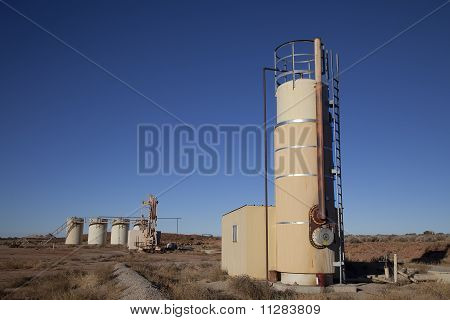 Oil well in the desert with blue sky poster