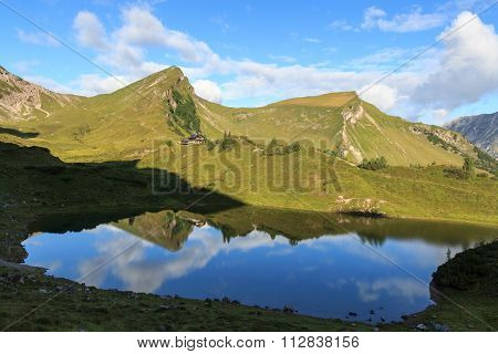 Mountain Rote Spitze and alpine hut Landsberger Hutte with reflection in lake