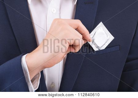 Male hand putting condom into breast pocket.