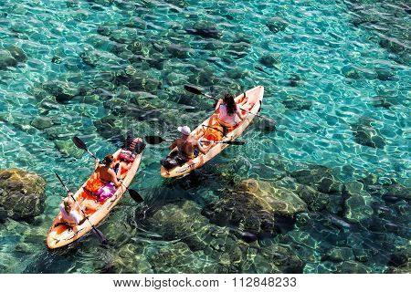 Tourists Kayaking At Tsigrado Beach In Milos Island, Cyclades, Greece