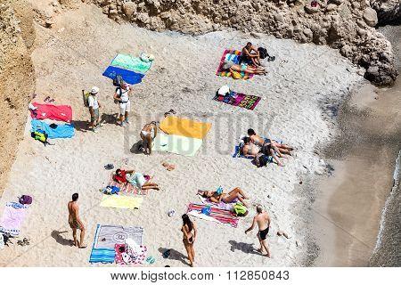 Tourists Sunbathing At The Beautiful Beach In Tsigrado Beach In Milos Island, Cyclades, Greece