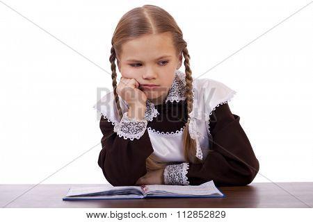 Sad schoolgirl sits at a school desk