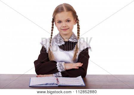 Young beautiful schoolgirl sitting at a desk, isolated on a white background