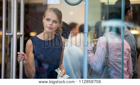 Pretty, young woman leaving a store/restaurant with cash in her hand after having paid for for the goods/food