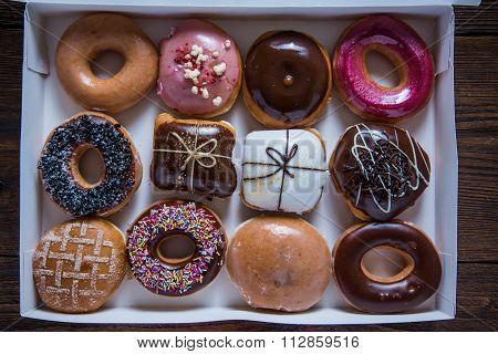 Dozen Artisan Donuts In Box On Table