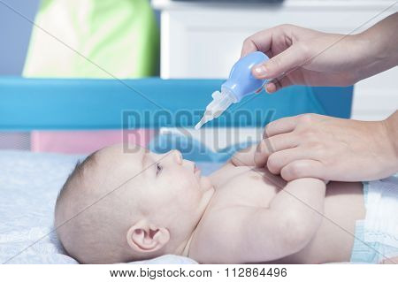 Mother using baby nasal aspirator. She is doing a mucus suction to three months baby boy poster