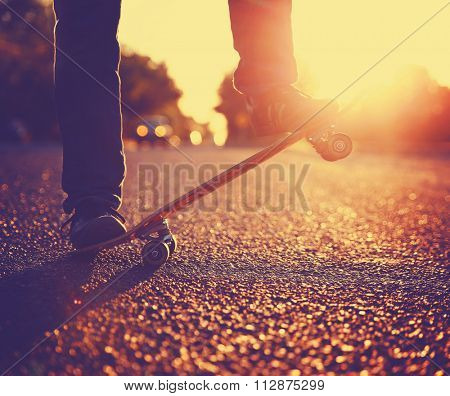Silhouette of Skateboarder jumping in front of a beautiful sunset on a freshly tarred road toned in a retro vintage instagram filter effect app or action