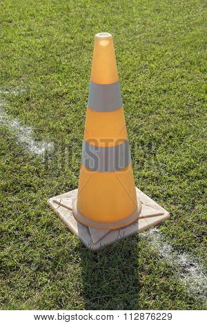 Traffic road cone pylon on green grass