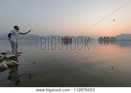 Local Man Feeding A Fish During Sunrise At Jal Mahal Water Palace Jaipur, India.