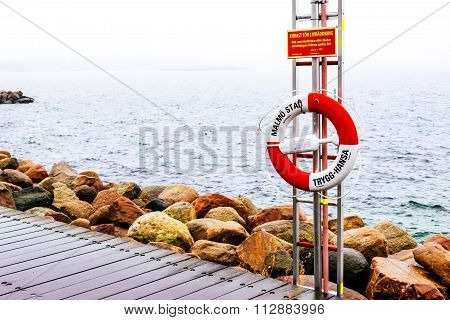 Malmo, Sweden - December 31, 2014: Wooden Docks And Life Belt By The Sea On Cloudy Day In Malmo, Swe