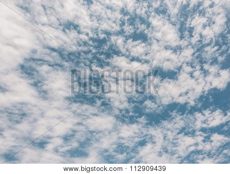 Fluffy white clouds and blue sky texture, film emulation filter applied