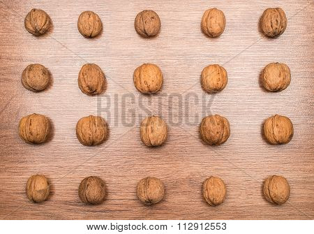 Different size wallnuts on wooden background in ordered pattern poster