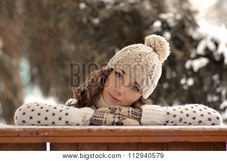 Very beautiful, pretty girl with hat, sweater, warm mittens, curly, brown hair in winter, snow bound forest look, you, curl up, put head on hands, put hands, turned, inclined head, tone, creative, beige, light, girl