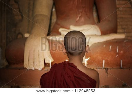 Rear view of young novice monk praying with candlelight inside a Buddhist temple, Bagan, Myanmar.