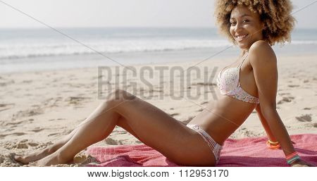 Young fit black woman wears white bikini and sitting on beach towel at beach