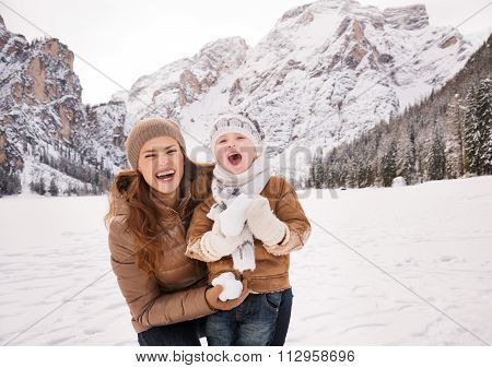 Mother And Child Playing With Snow Among Snow-capped Mountains