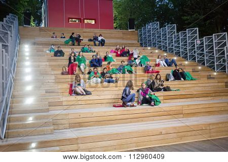 MOSCOW, RUSSIA - JUN 30, 2015: People sitting on wooden staircase of Open Air Cinema in Sokolniki.