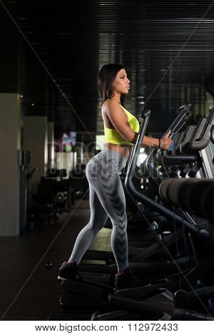 Latina Women On Elliptical Treadmill In Fitness Gym
