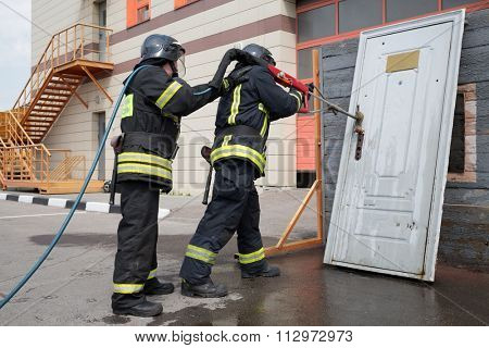 Two firefighters demonstrate lock snapping with wooden door