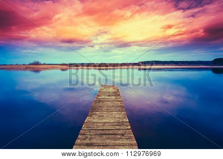 Colorful sunset dramatic sky over wooden boards pier on Calm Wat