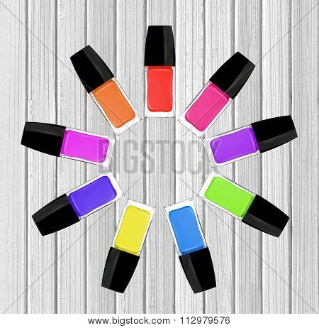 Set Of Colorful Nail Polishes On White Wooden Background