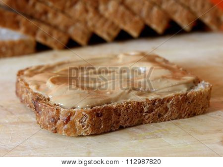 Peanut Butter And Bread On Wooden Chopping Board