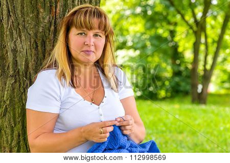Portrait Of 50-year-old Woman Engaged In Knitting In The Summer Park