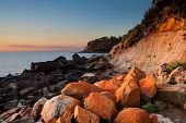 Seascape of Sunset with orange rocks on foreground poster