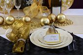 Happy New Years Eve elegant dinner table setting with black and gold decorations balloons and stylish centerpiece close up. poster