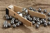 homemade bullet mold and ball-shaped bullets on burlap background poster