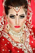 Portrait of a beautiful female model in traditional indian bridal costume with jewellery and makeup poster