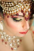 Portrait of a beautiful female model in traditional indian bride outfit with jewellery and makeup poster