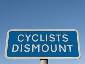 Cyclist dismount road sign against a clear blue sky poster