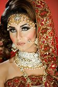 Portrait of a beautiful female model in traditional indian bridal costume with makeup and jewellery poster