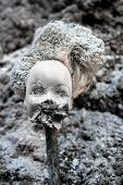 Beheaded girl doll with scary melted face on a grey ash background poster