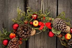 Christmas wreath made of juniper, nuts and pine cones on old wooden background