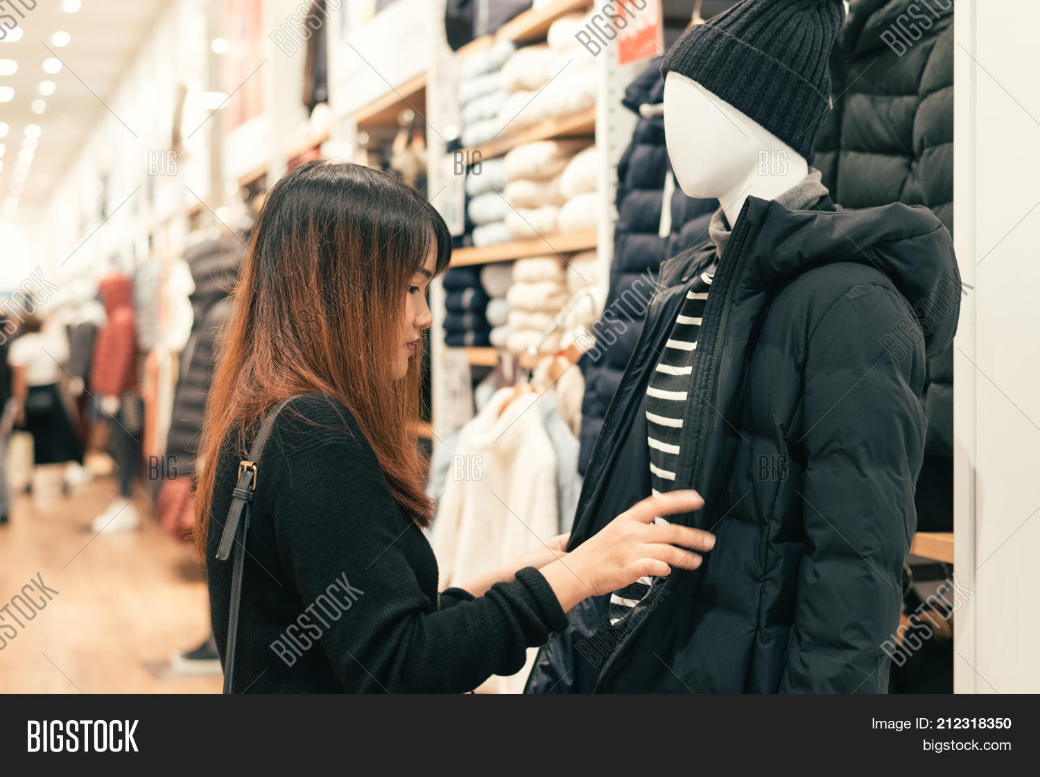 8f7bac8382c Half body shot of a happy asian young woman with shoulder bag looking at  clothes hanging