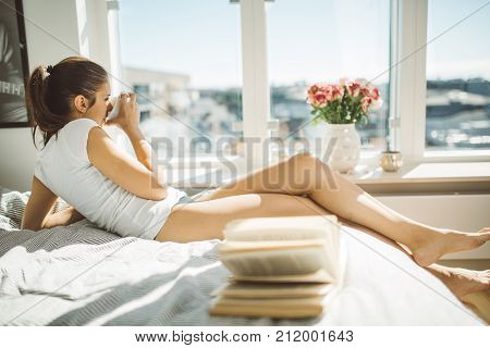 Portrait of a beautiful smiling woman enjoying fresh coffee in the sunny morning at cozy home.Leasure and relaxation concept.Perfect view.Hygge concept