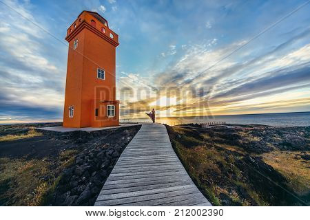 Abstract photo of woman act silhouette in dress in golden sunset near big orange lighthouse in Iceland.Fashion and nature concept artistic panorama.Western Icelandic untamed nature.Freedom