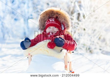Sled and snow fun for kids. Baby sledding in snowy winter park. Little boy in warm red jacket and knitted hat sitting in sheepskin footmuff. Kid on sleigh. Child on sledge. Family Christmas vacation.
