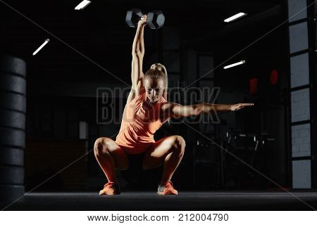 Beautiful sportswoman exercising at the gym doing overhead kettlebell squats copyspace motivation beauty confidence crossfit athletic body feminine powerful muscles weight gain concept