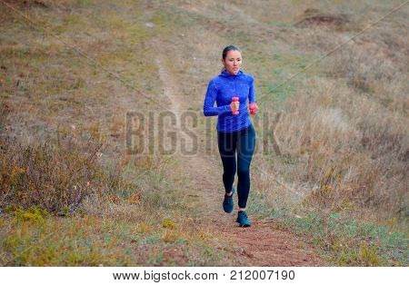 Beautiful Athletic Girl With Pink Dumbbells  Runs Along The Hilly Autumn