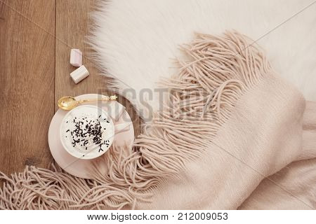 Cozy Winter Mornings. Cappuccino And A Warm Scarf On A White Fur Carpet On The Floor