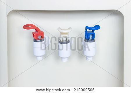 Close-up of hot and cold faucet of water dispenser. Water refrigerator.