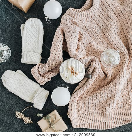 Women's winter clothes look on grey plaid. Warm beige sweater and white knitted mittens gift box and glass balls. Christmas fashion composition. Flat lay top view.