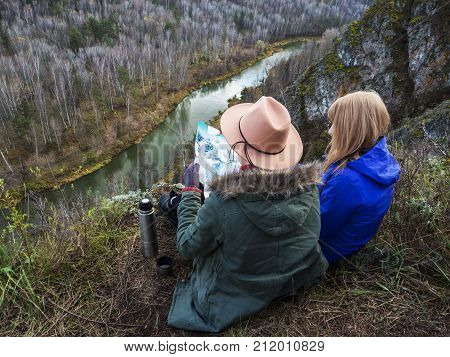 The girls were lost in the mountains near a beautiful river.They look at the map and use the compass to look for the direction of the path. Hot coffe in thermos.