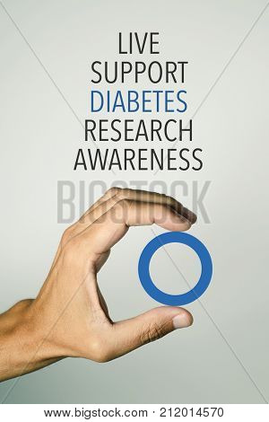the hand of a young man with a blue circle, symbol of diabetes, and words related to the support of affected by diabetes, such as live, research or awareness