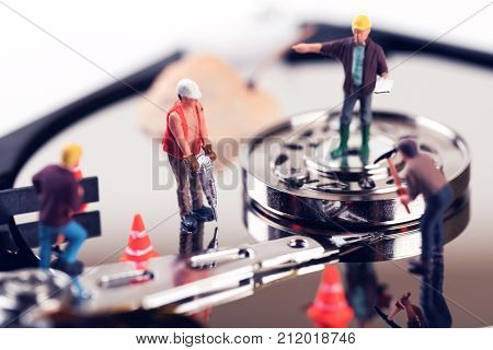 data recovery concept. construction worker figurines on hard disk drive