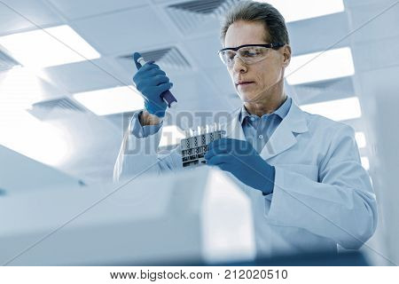 Genius scientists. Smart nice serious man holding test samples and doing a research on them while working in the lab