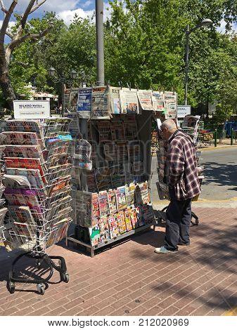 ATHENS GREECE - APRIL 23 2017: Man reads Sunday newspaper headlines at outdoors newsstand.